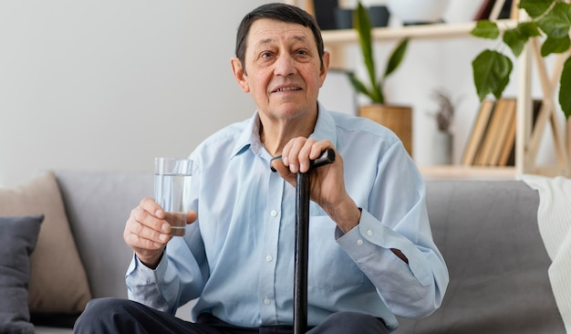 Uomo del colpo medio che tiene un bicchiere con acqua
