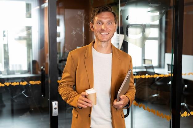 ノートパソコンとコーヒーカップを保持しているミディアムショットの男