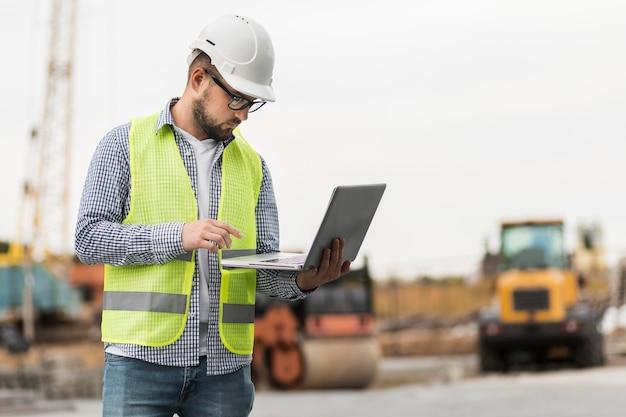 Medium shot man holding laptop
