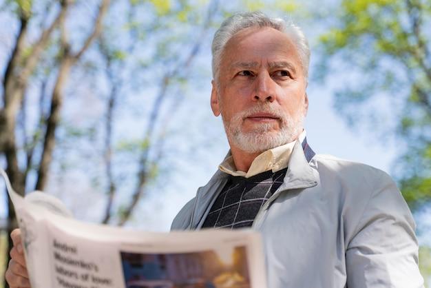중간 샷 남자 지주 신문