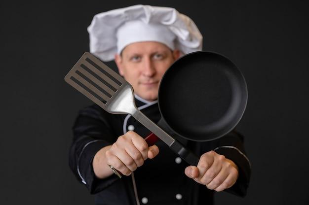 鍋とヘラを持っているミディアムショットの男
