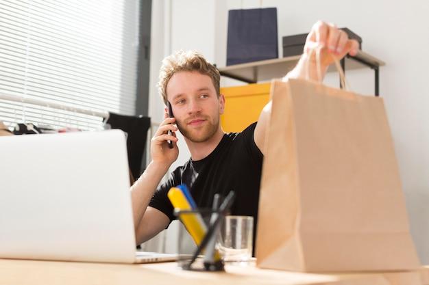 Medium shot man holding paper bag