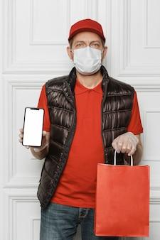 電話とバッグを持っているミディアムショットの男