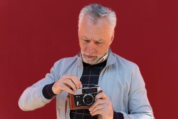 Uomo a colpo medio che tiene in mano una macchina fotografica