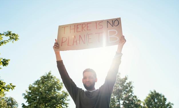 Средний выстрел мужчина держит плакат