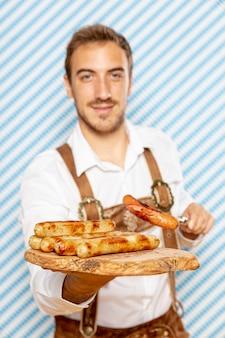 Medium shot of man holding plate of german sausages