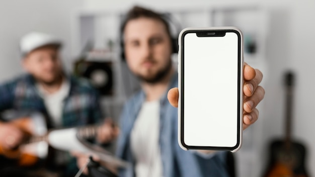 Medium shot man holding smartphone