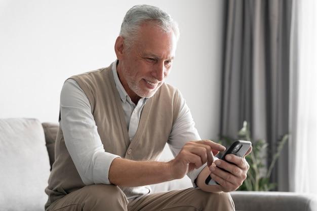 Средний выстрел мужчина держит смартфон
