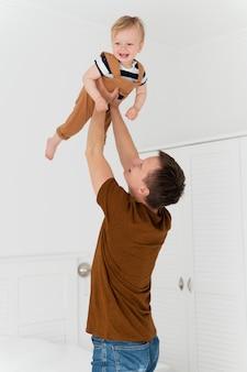 Medium shot man holding up kid