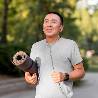 Средний снимок человека, держащего коврик для йоги