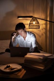 Средний снимок человека в постели с ноутбуком