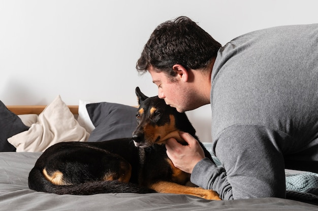 ミディアムショットの男が犬にキス