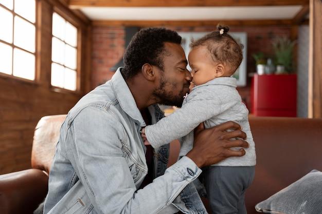 ミディアムショットの男が子供にキス