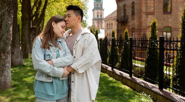 Uomo del colpo medio che bacia la donna sulla fronte