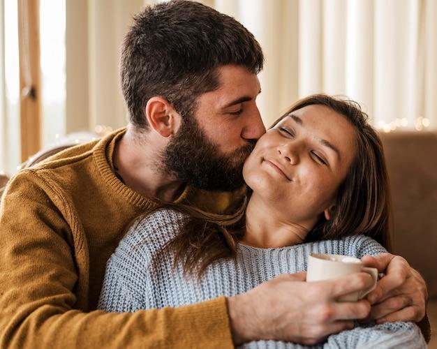 Мужчина среднего выстрела целует женщину в щеку