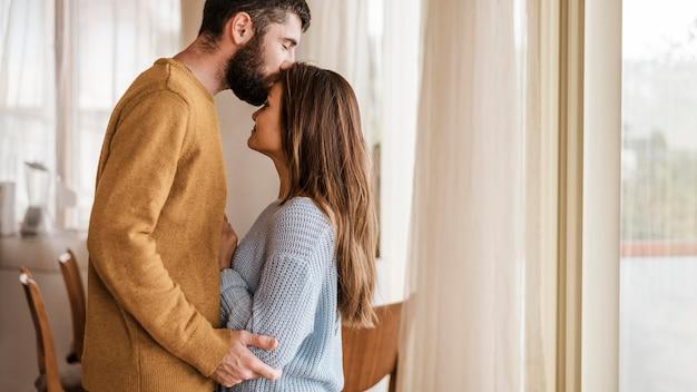 Средний выстрел мужчина целует женщину в лоб