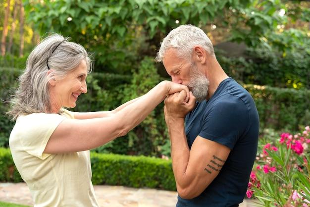 Medium shot man kissing woman's hands