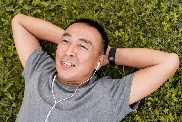 Medium shot man laying on grass