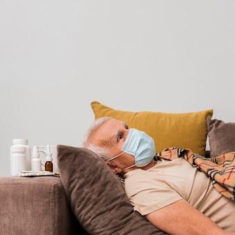 マスクとソファに横たわっているミディアムショットの男