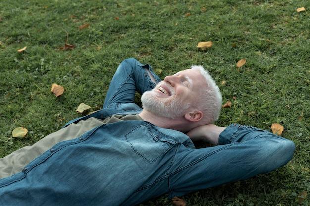 草の上に横たわるミディアムショットの男