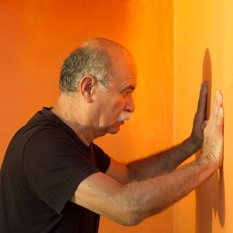 Medium shot of man leaning on an orange wall