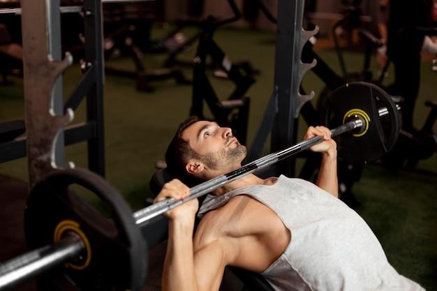 Medium shot man lifting bar with weights