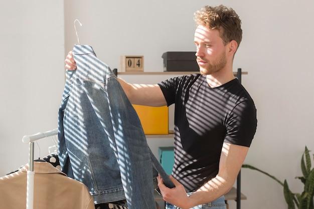Uomo del colpo medio che esamina la camicia del denim
