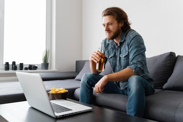 Uomo del colpo medio che esamina il computer portatile
