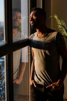 Uomo del colpo medio che guarda fuori dalla finestra