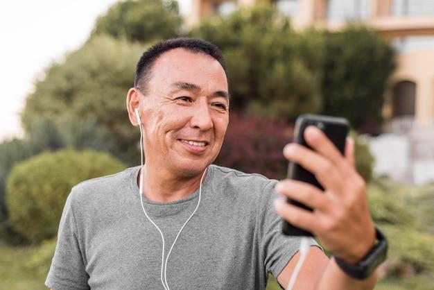 Uomo del colpo medio che esamina smartphone