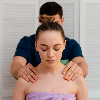 Uomo di colpo medio che massaggia donna