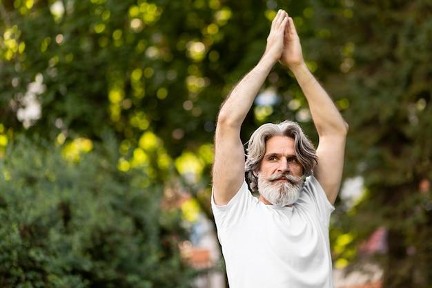Uomo del colpo medio che medita all'aperto