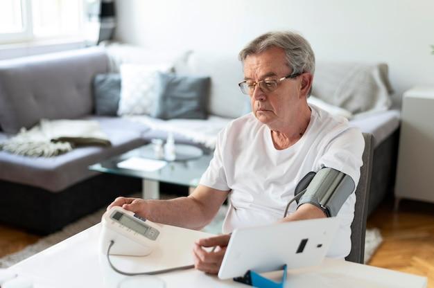 Medium shot man monitoring hid blood pressure