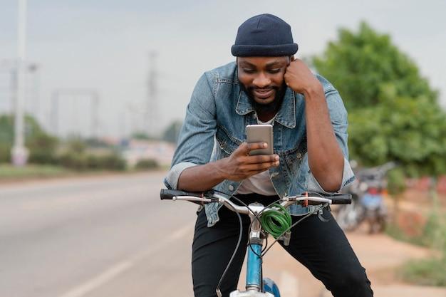 Средний выстрел человек на велосипеде с телефоном