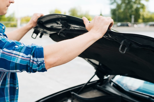 Medium shot of man opening car hood