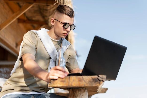 Средний выстрел человека на открытом воздухе с ноутбуком