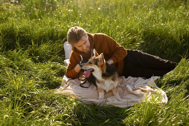 ミディアムショットの男が犬をかわいがる