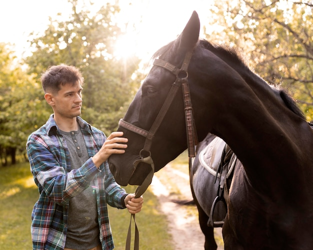 Medium shot man petting horse in nature