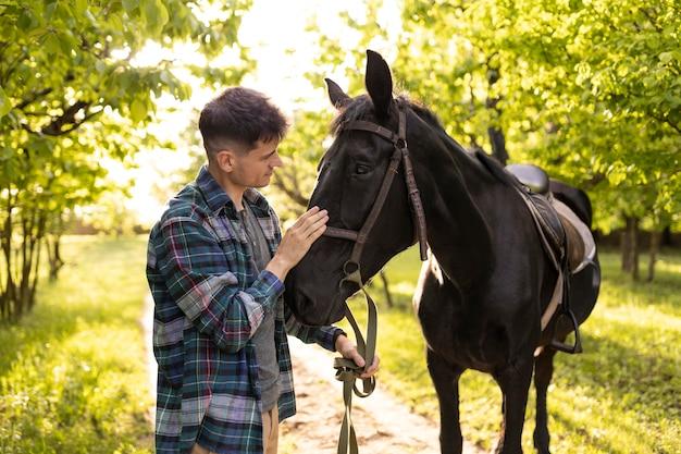 Uomo di tiro medio che accarezza il cavallo