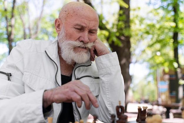 Uomo di tiro medio che gioca a scacchi