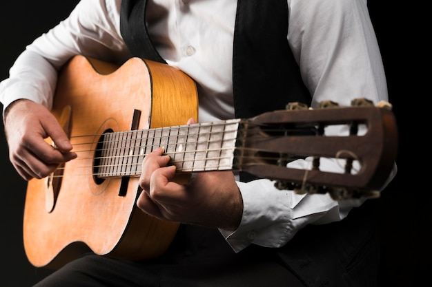 Uomo del colpo medio che gioca la chitarra classica