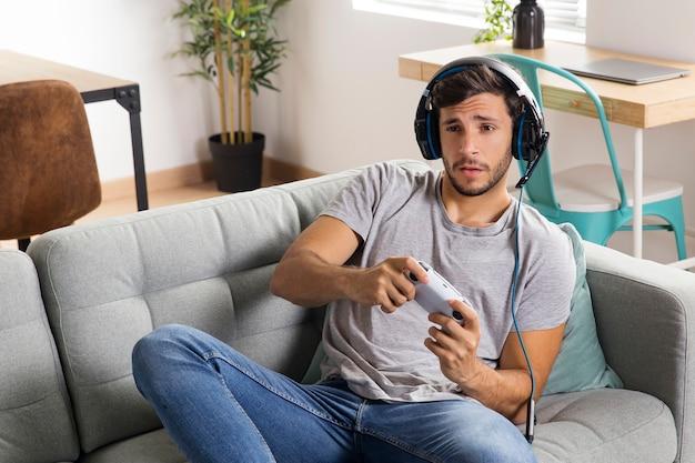 Uomo di tiro medio che gioca sul divano