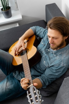 自宅でギターを弾くミディアムショットの男
