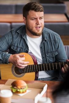 テーブルでギターを弾くミディアムショットの男