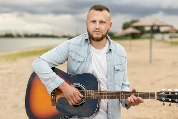Medium shot man playing the guitar on a beach