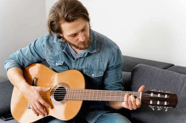 ソファでギターを弾くミディアムショットの男
