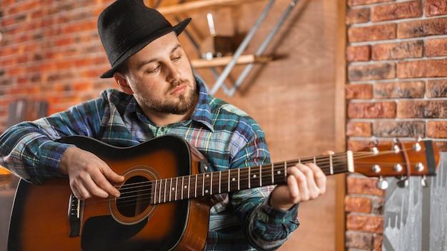 Uomo del colpo medio che suona uno strumento