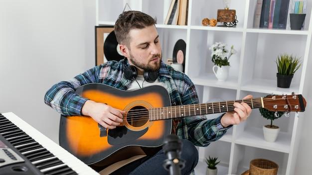 중간 샷 남자 기타 연주