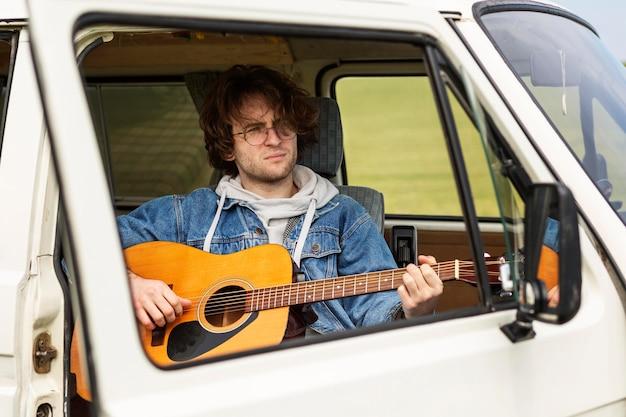 ギターを弾くミディアムショットの男