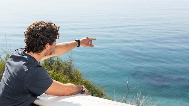 Medium shot man pointing at sea